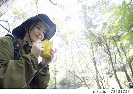 山歩き中飲み物を飲んで休憩をする女性 トレッキングイメージ 72581737