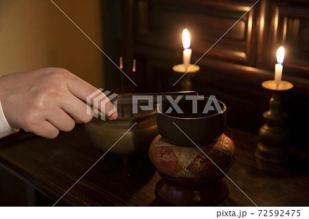 日本の家庭の仏壇でお線香に火をつける様子 ろうそく 72592475