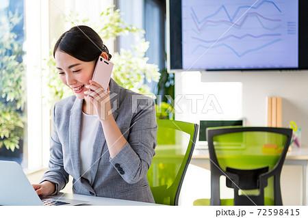 明るいオフィスでスマホで会話するビジネスウーマン 72598415