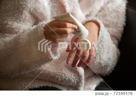 アルコール消毒で荒れた手をハンドクリームを塗ってケアする女性の手元 72599576