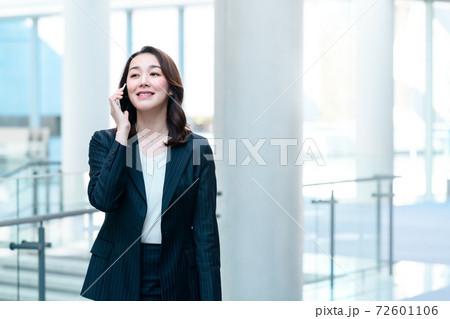 オフィスの廊下で電話をするビジネスウーマン 72601106