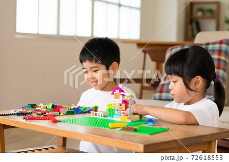 リビングのテーブルでブロック遊びする姉弟 72618553