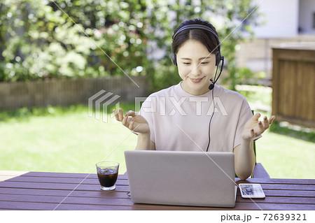 庭でアイスコーヒーを飲みながらテレワークをする若い女性 72639321