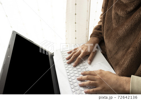 温かい恰好でノートパソコンを使う男性 72642136