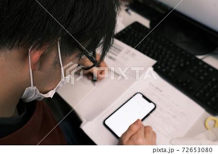 スマホで調べ物(勉強)をするマスク姿の大学院生 72653080