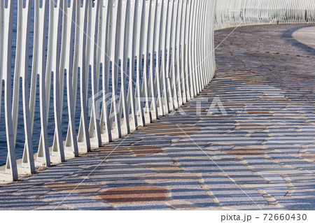 白いフェンスの柱と石畳に落ちるフェンスの影 72660430