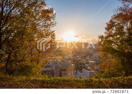 高台の木々の隙間から見えた太陽と夕焼けの街並み 72662871