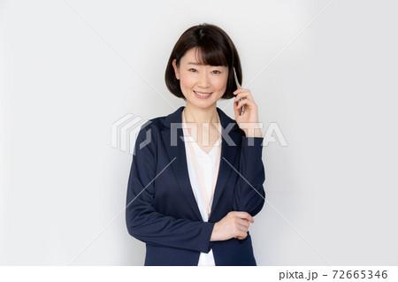 白背景のスマホで会話をする笑顔の女性のポートレート 72665346