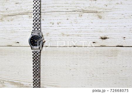 木製テーブルに置かれたシルバーの腕時計 72668075