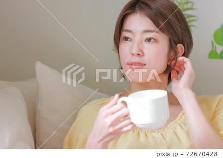 コーヒーカップを持ち耳のあたりを触る女性 72670428