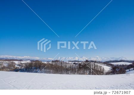 晴れた日の冬の丘陵地帯と山並み 十勝岳連峰 72671907