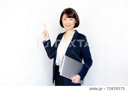 白背景のノートパソコンを持って指差しポーズをする女性のポートレート 72676575