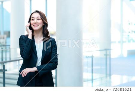 オフィスでスマホで電話するスーツ姿のビジネスウーマン 72681621