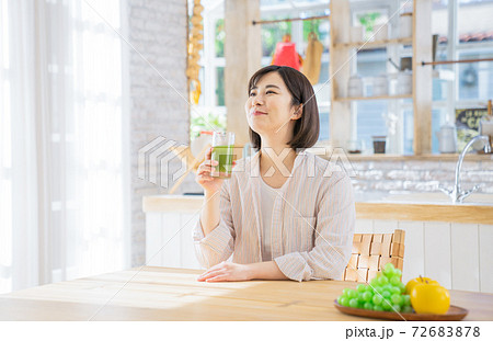 野菜ジュースを持ってくつろぐ若い女性 72683878
