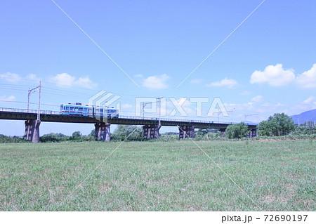 夏の青空の下、鉄橋を渡る路面電車 72690197