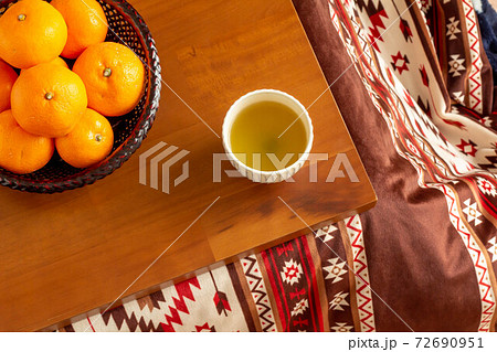 炬燵に置かれたみかんと温かい緑茶 72690951