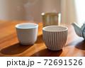 温かいほうじ茶の入った湯飲みと急須 72691526