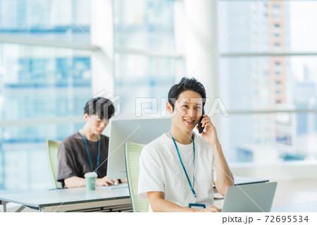【オフィスカジュアル】電話をする軽装のエンジニア 72695534