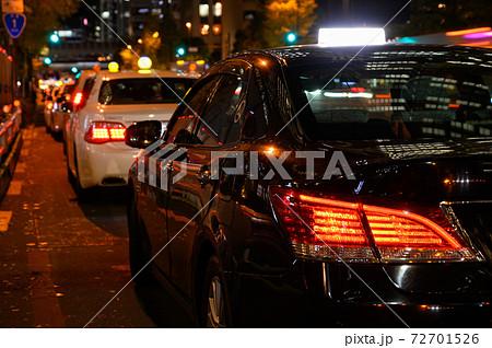 夜に客待ちをするタクシー 72701526
