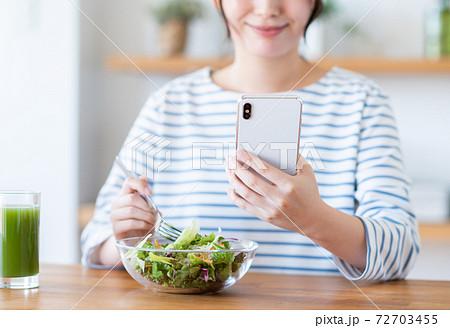 スマホを見ながらサラダを食べる若い女性 72703455