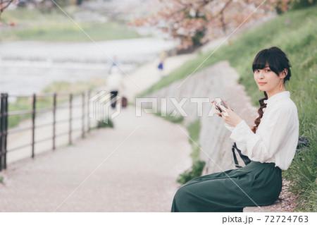 桜の背景とカメラを持っている白いシャツの女性 72724763