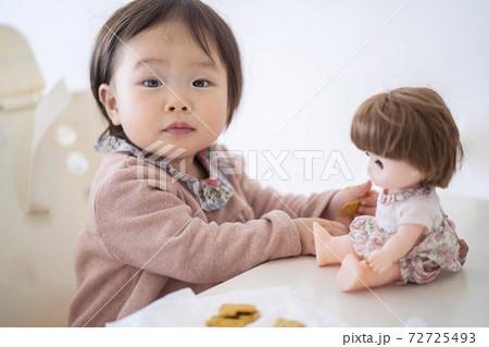 人形にビスケットをあげる赤ちゃん 72725493