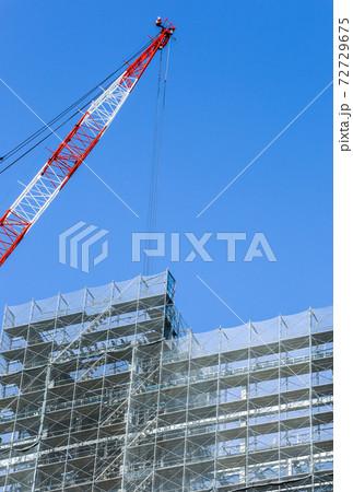 大型クレーンを見る建設中の高層ビル 72729675