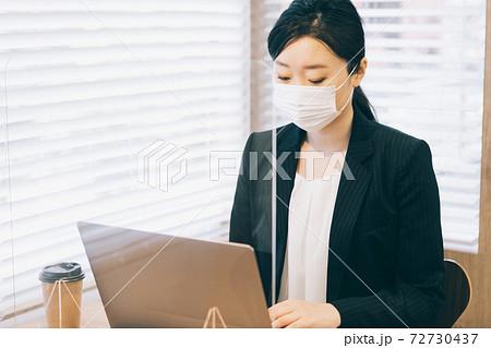 飛沫防止のアクリル板の前で仕事をするマスクの女性 72730437