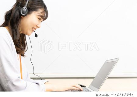 ヘッドセットをつけてリモートワークをする女性 72737947
