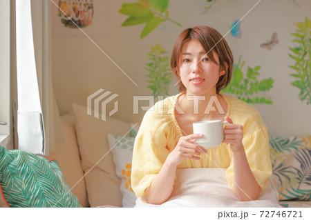 コーヒーカップを両手で持ち視線を上げた女性 72746721