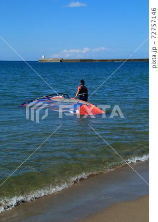 ウインドサーフィンを沖へ運ぶ男性 72757146