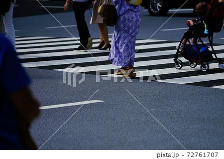 都会の横断歩道を歩く浴衣姿の人やベビーカーを押す歩行者 72761707