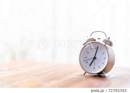 窓辺の机の上に置かれた朝日に照らされる目覚まし時計 72763565