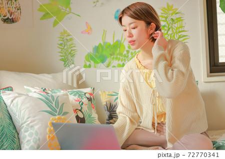 ノートPCを見ながら髪を触る女性 72770341