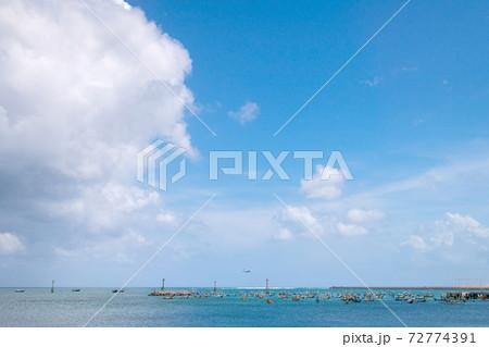 たくさんの船の浮かぶ海の向こうの滑走路と飛行機 72774391