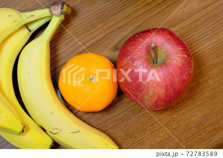 机の上に置かれたりんごとバナナとみかん 72783589