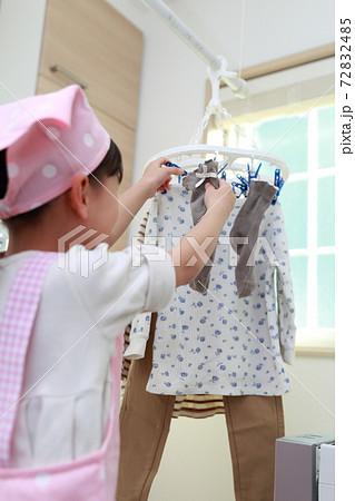 洗濯物干しを手伝う5歳の女の子 72832485