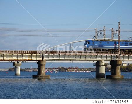 鉄橋を行く貨物列車の先頭車両と川のある風景 72837343