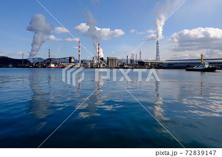 工業地帯の工場、工場から上る煙が海に写り込んでいるリフレクション 72839147