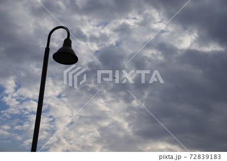 曇り空をバックにした街灯と曇り空を飛ぶヘリコプター 72839183