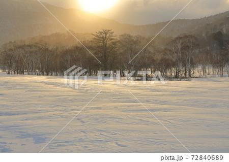 夜明けの雪原と林に雲間からの太陽の光 72840689