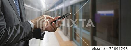 駅のホームでスマートフォンを操作しているビジネスマン 72841293