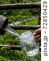 Big Glass Filled With Clear Mountain Drinking Water From A Wooden Spring 72850429