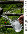 Big Glass Filled With Clear Mountain Drinking Water From A Wooden Spring 72850433