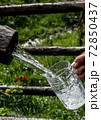 Big Glass Filled With Clear Mountain Drinking Water From A Wooden Spring 72850437