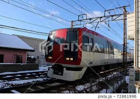雪が積もる住宅の間を走り抜けていくローカル電車 72861996