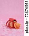 ピンクの背景に桜と、粘土で作られた赤色のランドセル、黄色い帽子 72870568