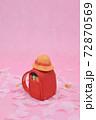 ピンクの背景に桜と、粘土で作られた赤色のランドセル、黄色い帽子 72870569