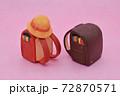 ピンクの背景に粘土で作られた赤色と茶色のランドセル、黄色い帽子 72870571