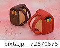 ピンクの背景に粘土で作られた赤色と茶色のランドセル 72870575